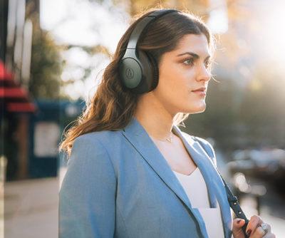 Kvinna i blå kavaj med ATH-ANC700BT hörlurar på sig.