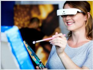 Kvinna står framför stafli och målar med eSight glasögon på sig